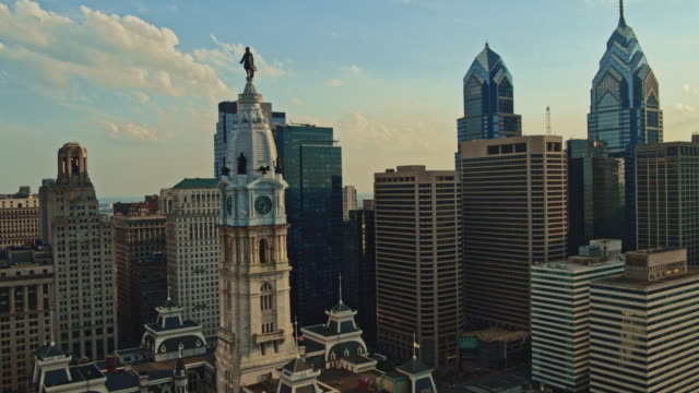 Aerial close view on Philadelphia City Hall with the William Penn statue atop of the tower in front of Downtown District, Philadelphia, Pennsylvania. Drone video with the panoramic orbiting camera motion.