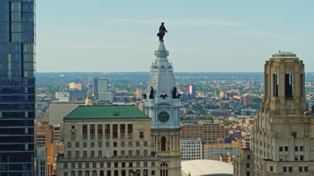 Aerial close view on Philadelphia City Hall with the William Penn statue atop of the tower in front of the cityscape of Philadelphia, Pennsylvania. Drone video with the panning camera motion.
