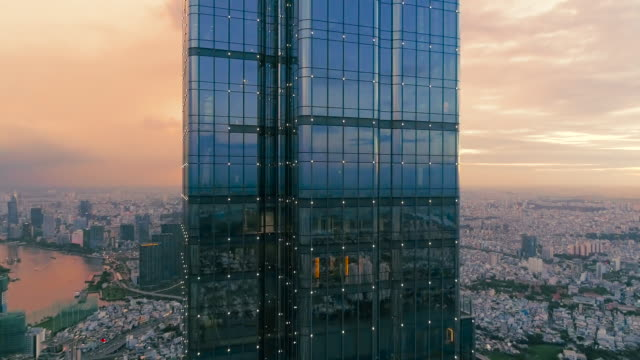 Aerial: Closeup of skyscraper with reflections of sunset followed by revealing cityscape.