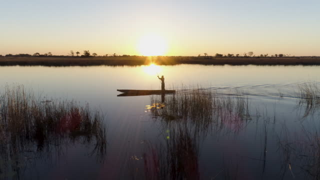 Aerial close-up panning view of one poler silhouetted against the setting sun rowing a Mokoro video