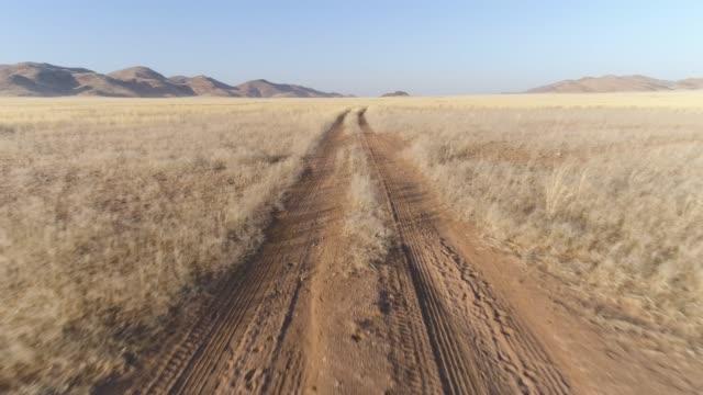 4k aerial close-up view of a sand road in the koakoland savannah region of the namib desert, namibia - wiejska droga filmów i materiałów b-roll