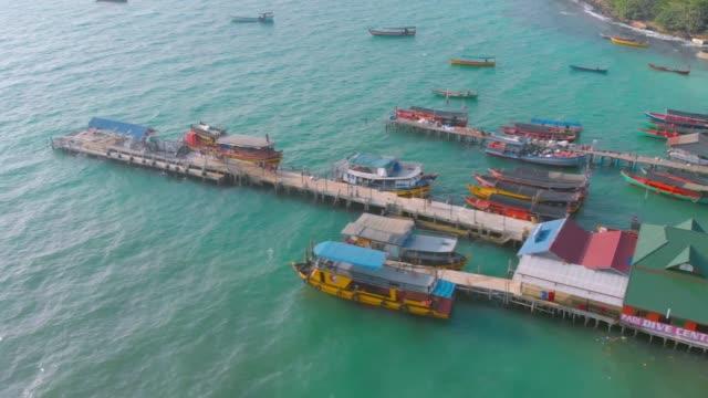 luftaufnahme von langgestreckten booten, die am pier der insel koh rong in kambodscha parken - kambodschanische kultur stock-videos und b-roll-filmmaterial