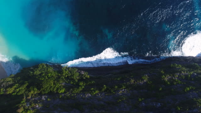 Aerial Coastline view and waves crashing on rocky cliff shoreline. video