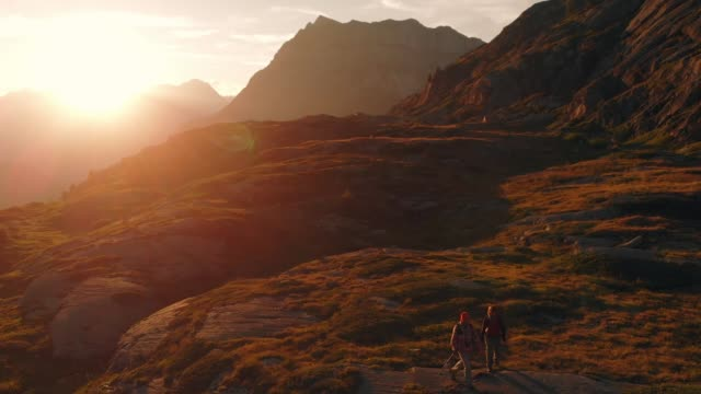 Aerial: couple backpackers hiking to the mountain top in backlight, slow motion