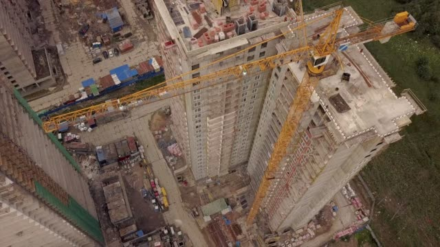 Aerial day fly over under construction new modern building work builders and technicals with crane Aerial day fly over under construction new modern building work builders and technicals with crane. High height of the multi-floor flat house. cement stock videos & royalty-free footage