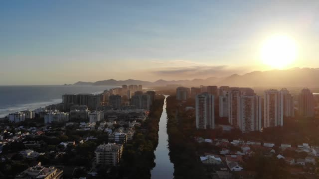 Aerial descending footage of Marapendi canal in Barra da Tijuca, filmed against the setting sun. Tall residential skyscrapers on one side, and beach on the other. Rio de Janeiro, Brazil video