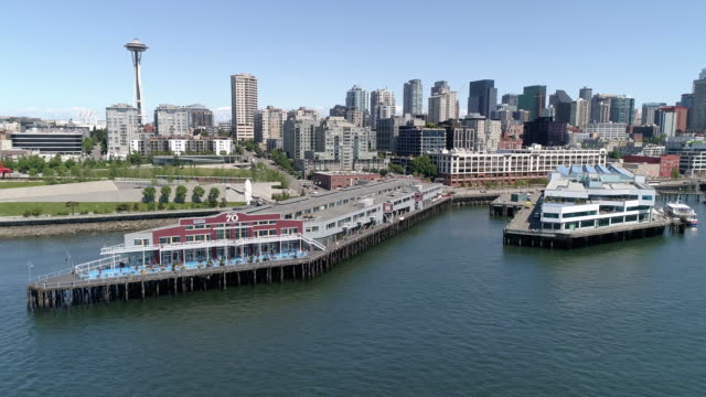 Aerial Dolly Across Downtown Seattle Buildings and Waterfront Pier 70 on Sunny Day with Blue Sky video