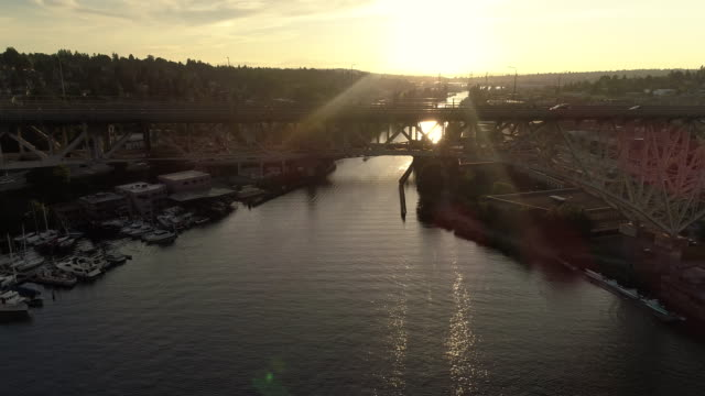 Aerial Dolly of Cars Commuting Across Water Canal on Big City Bridge at Sunset video