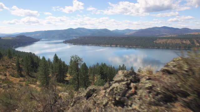 空中のドリー撮影大きな湖となだらかな丘を明らかにするための砂漠の岩 ビデオ