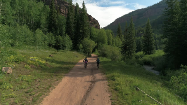 Aerial Drone bikers on dirt road Colorado forest between the Rocky Mountains 4k 60fps
