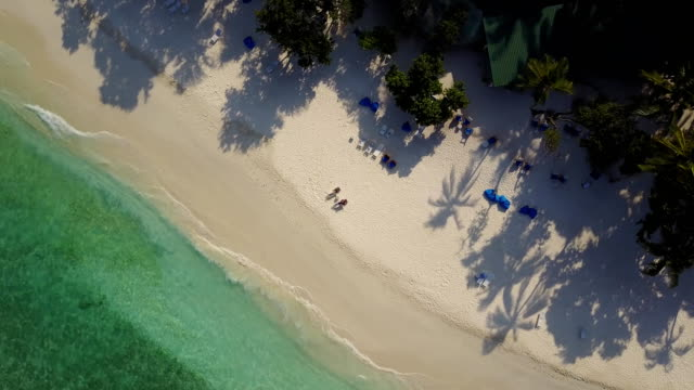 aerial drone camera ascending and rotating high above the couple in love lying in the sun on beach bed deck chairs and drinking cocktails at empty tropical white sand beach on atoll island resort with palm trees shadows and turquoise indian ocean on - località turistica video stock e b–roll