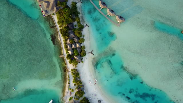 Aerial drone camera is descending to tropical island with white sand beach and resort with palm trees shadows, bungalows and turquoise Indian ocean on Maldives video