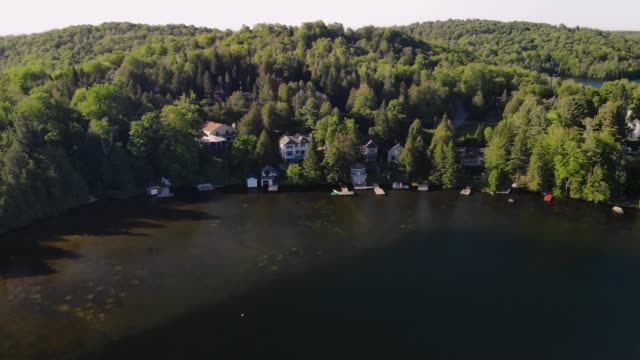 4k luftbild drohne ferienhaus haus see fliegen nach vorn über ferienhäuser - landhaus stock-videos und b-roll-filmmaterial