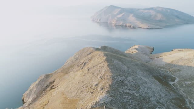 海の上の日の出の間にクロアチアのバスカの近くの島のクルクの上に夏の空中ドローン飛行 ビデオ