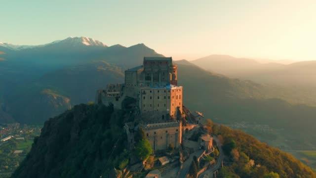 stockvideo's en b-roll-footage met luchtfoto: drone vliegen op oude middeleeuwse abdij zat op de bergtop - turijn, italië - klooster