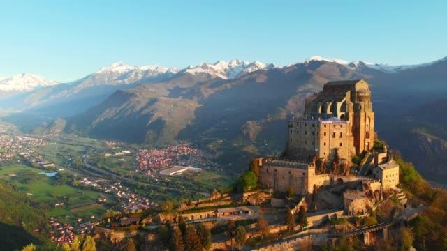 vídeos de stock, filmes e b-roll de aéreo: drone voando a velha abadia medieval empoleirada no topo de uma montanha - turim, itália - castelo