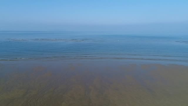 aerial drone flying, dolly in of calm, sea shallow tideland video