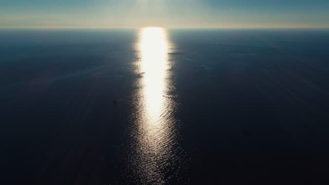 Aerial - Drone - Flying towards the sun over the sea at high altitude and low speed video