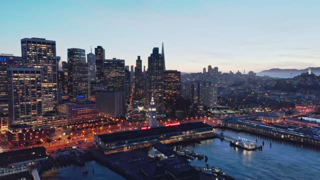 Aerial drone flythrough of the San Francisco city skyline and Ferry Building at night