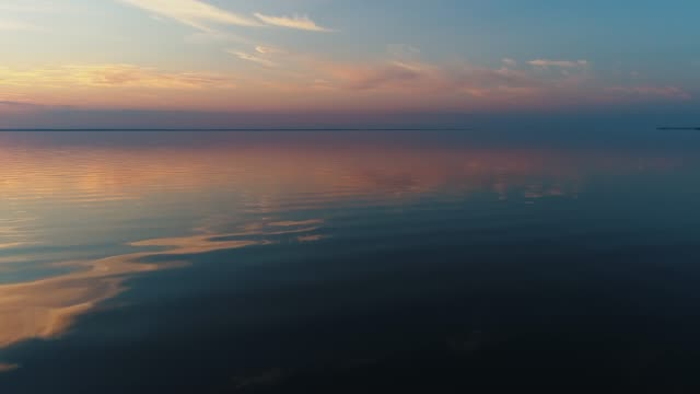 aerial drone footage. fly over calm water to sunset - спокойная вода стоковые видео и кадры b-roll