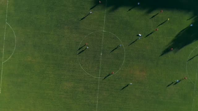 Aerial drone footage. Fly over soccer players on field rotate shot