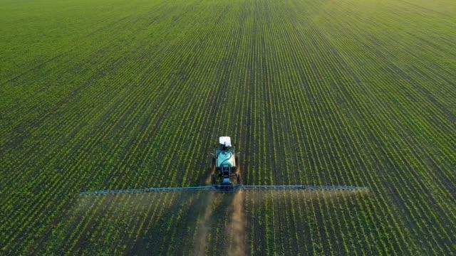 4k aerial drone footage. following tractor sprayer on soybean fields - fertilizzante video stock e b–roll