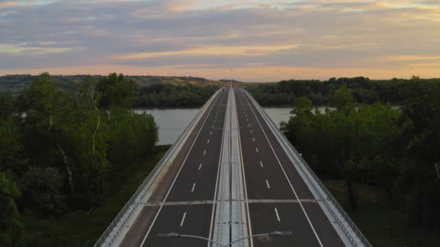 vídeos de stock e filmes b-roll de aerial drone footage: long haul semi truck driving on the empty highway across bridge. landscape and river in the background - covid flight