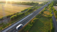 istock Aerial Drone Footage: Long Haul Semi Trucks Driving on the Busy Highway in the Rural Region of Italy. Agricultural Crop Fields and Hills in the Background 1182509922