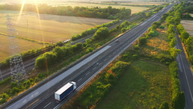 aerial drone footage: long haul semi trucks driving on the busy highway in the rural region of italy. agricultural crop fields and hills in the background - тягач с полуприцепом стоковые видео и кадры b-roll