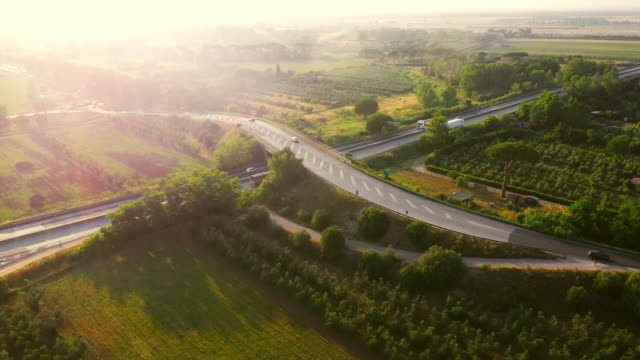 aerial drone footage: long haul semi trucks driving on the busy highway in the rural region of italy. schöne landschaft der natur und menschliche logistik fortschritt - autotransporter stock-videos und b-roll-filmmaterial