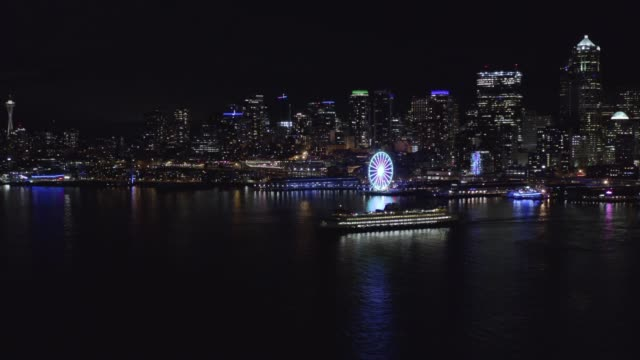 Aerial drone footage of a ferry departing Downtown Seattle at night