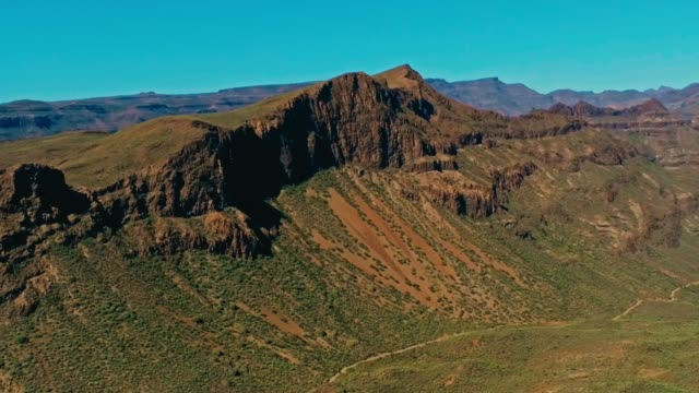 aerial drone footage of beautiful stunning landscape view off the degollada de la yegua viewpoint with cliff rock peaks and valley with a curvy road on a sunny day - cespuglio tropicale video stock e b–roll