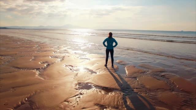 stockvideo's en b-roll-footage met luchtfoto drone beelden van fit vrouw permanent op strand - handen op de heupen
