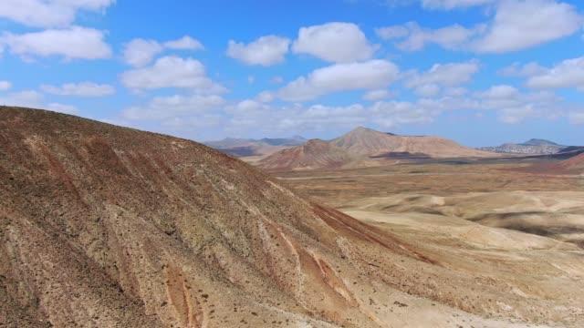 aerial drone bilder av montana roja (red mountain), en slocknad vulkan, en del av parque natural de corralejo på ön fuerteventura, kanarieöarna, spanien. lajares by i bakgrunden. - utdöd bildbanksvideor och videomaterial från bakom kulisserna