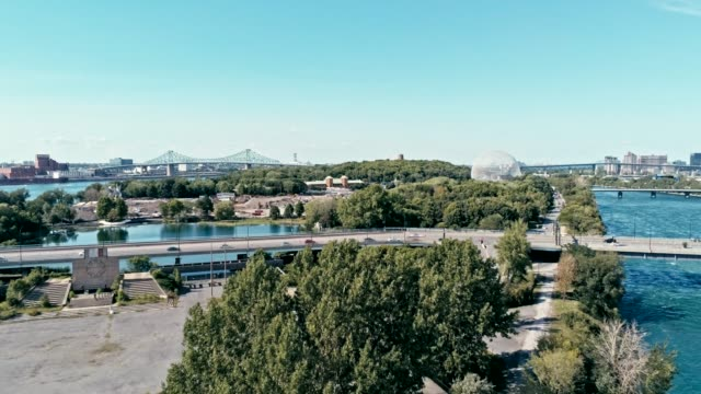 aerial drone footage of montreal with bridges and a park area plus ile sainte helene island with the biosphere dome in the background - struttura pubblica video stock e b–roll
