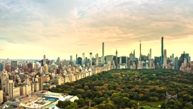 Aerial drone footage of New York skyline at sunset Aerial drone footage of New York midtown skyline at sunset viewed from above Central Park, with slow camera panning central park manhattan stock videos & royalty-free footage
