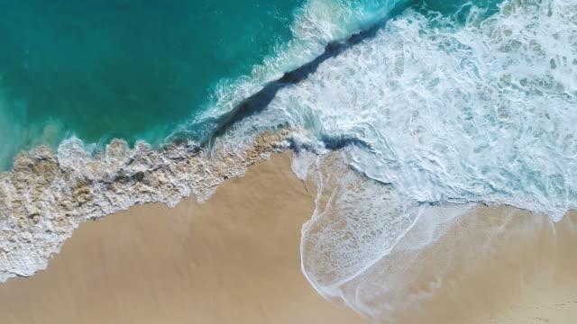 Aerial drone footage of ocean waves reaching shore.