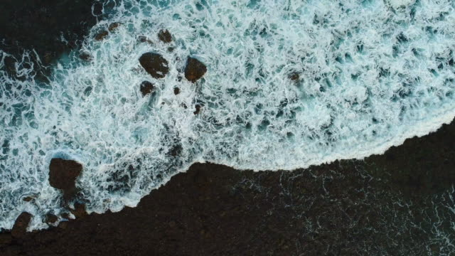 Aerial drone footage of ocean waves washing up on rock at beach. video