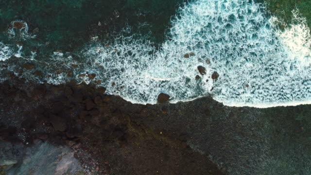 vídeos de stock, filmes e b-roll de filmagem aérea zangão das ondas do mar lavando na rocha na praia. - erodido