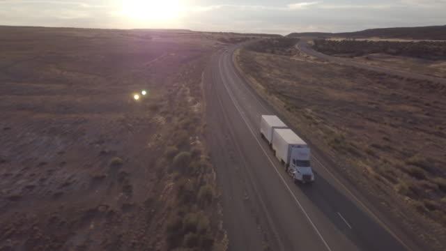 aerial drone footage of semi-trucks rolling down the highway - колонна стоковые видео и кадры b-roll