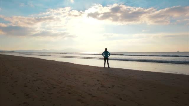 stockvideo's en b-roll-footage met luchtfoto drone beelden van sportieve vrouw stond op strand - handen op de heupen