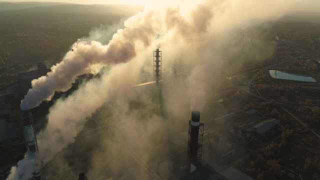 Aerial drone footage of steel factory pipes during sunset time