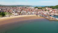 istock Aerial drone footage of the beach front in the town of Scarborough in North Yorkshire, England UK showing people relaxing and having fun on the beach on a sunny summers day 1323560630