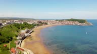 istock Aerial drone footage of the beach front in the town of Scarborough in North Yorkshire, England UK showing people relaxing and having fun on the beach on a sunny summers day 1323560870