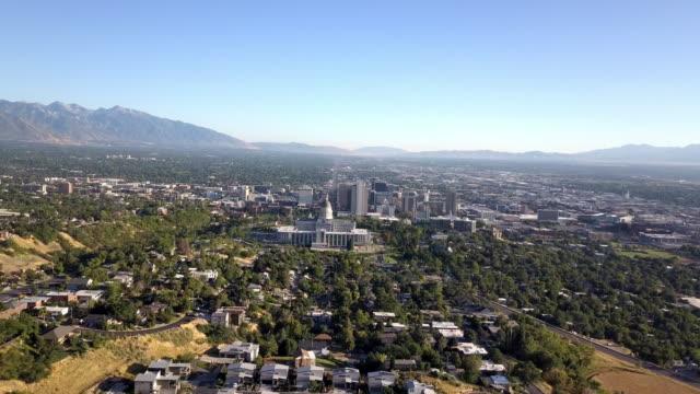 vidéos et rushes de images aériennes de drone du bâtiment de capitol d'état de l'utah et des gratte-ciel et des maisons résidentielles environnantes de centre-ville au crépuscule dans l'heure d'été - lac salé