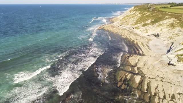 aerial drone footage of waves bouncing on rocks at the beach. beautiful blue turquoise sea atlantic ocean. tracking in. guetary, south france. beautiful landscape in 4k. - western australia stock videos & royalty-free footage