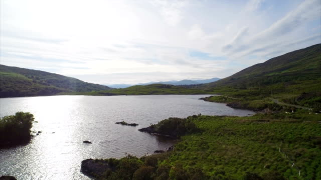 vídeos de stock e filmes b-roll de aerial drone footage over and lake and valley - margem do lago