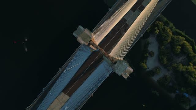 vídeos de stock e filmes b-roll de aerial drone footage. top view circle south bridge in kyiv at sunset - ponte