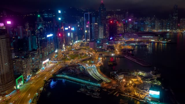 Aerial drone hyper lapse or time lapse over Hong Kong Victoria Harbor at night.