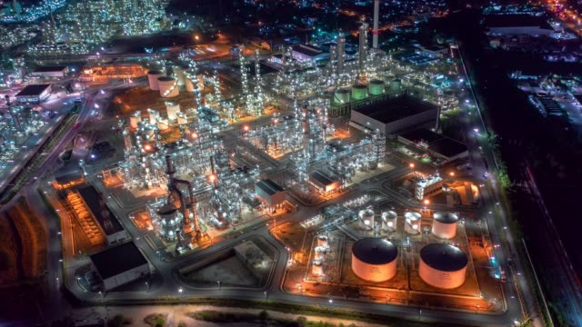 aerial drone hyper lapse over oil refinery factory at night with many storage tanks and pipelines. shot by 4k high resolution drone. - очистительный завод стоковые видео и кадры b-roll
